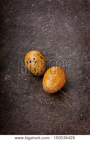 Colored quail eggs by Easter on a brown surface.