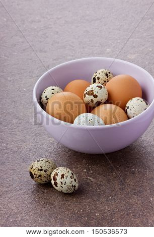 Chicken and quail eggs by Easter in a ceramic bowl on a brown surface.