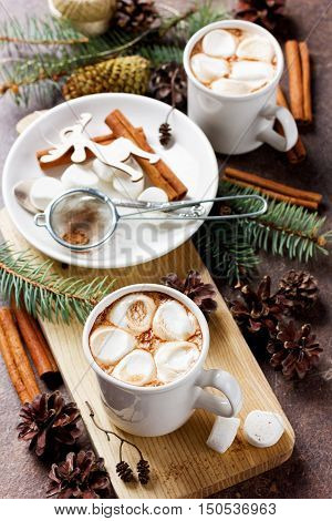 Cup of cocoa or chocolate with marshmallows on wooden background decorated with spruce, cinnamon sticks and pine cones. Christmas or new year lifestyle.