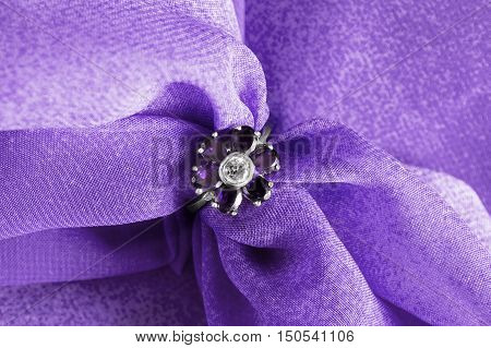 Amethyst flower shaped ring on purple cloth as a background