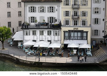 LUCERNE SWITZERLAND - MAY 02 2016: Aerial view towards two neighboring cafes. Coffee tables and white umbrellas are placed outside buildings in close proximity to the banks of the River Reuss.