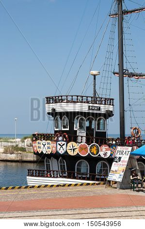KOLOBRZEG POLAND - JUNE 22 2016: Billboard placed beside moored at the wharf cruise ship called The Pirate encourages to cruise on board this ship