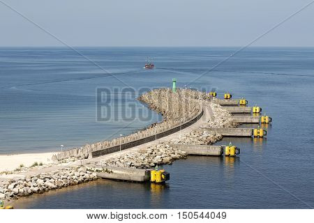 KOLOBRZEG POLAND - JUNE 22 2016: Breakwater with the green lighthouse placed on its end. It was built to protects the waterway to the sea port from the action of the waves
