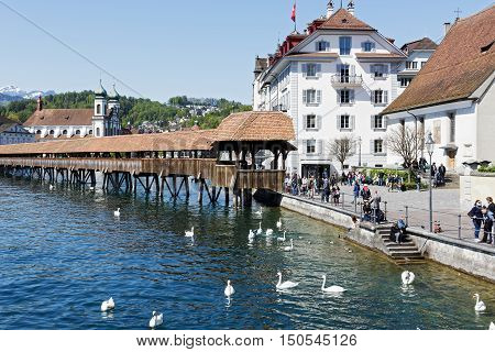 LUCERNE SWITZERLAND - MAY 05 2016: Entry to roofed wooden the Chapel Bridge that connects the two banks of the river Reuss can be seen on the right side of the river