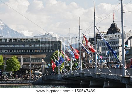 LUCERNE SWITZERLAND - MAY 04 2016: Flags of Switzerland and cantonal waving on the masts fixed to the Seebruecke Bridge that connects the historical and contemporary parts of the city