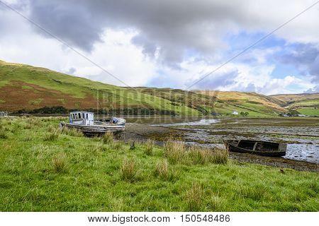 Beautiful Isle of Skye Scotland landscape. Three old abandoned wooden boat wrecks on the shore at Loch Harport