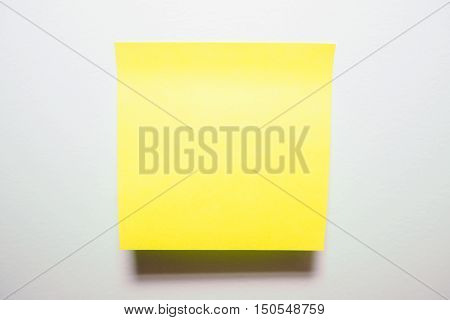 Yellow stick note paper post it on white wall background.