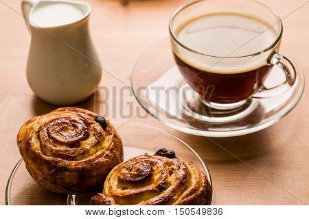 Coffee cup with cinnabon and milk jug on wooden background. Top view.