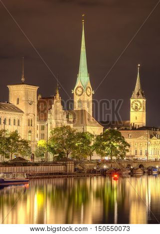 Historic buildings along the Limmat river, towers of the Fraumunster Cathedral and St. Peter Church in the city of Zurich, Switzerland at night. A HDR image with tone mapping applied.
