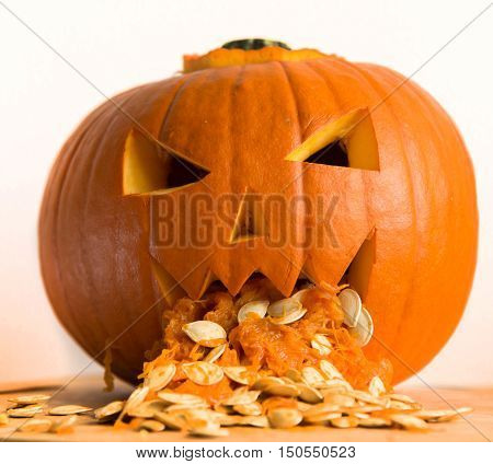 Pumpkin Puking With Pumpkin Seeds On Wood Table And White Background