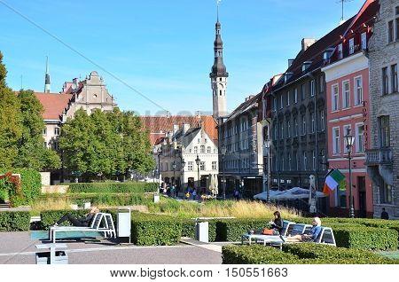 Tallinn Estonia - September 06 2016: People are resting in the garden near St. Nicholas Church in Tallinn at sunny day.