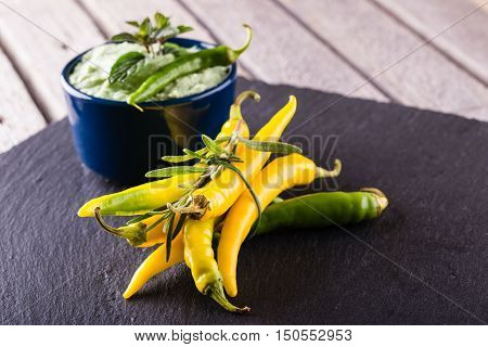 Bunch Of Yellow And Green Chili Pepers With Dip In Blue Bowl