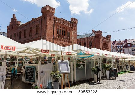 KOLOBRZEG POLAND - JUNE 23 2016: Temporary cafes and restaurants covered with a square umbrellas open for the summer season and behind them the Town Hall building built of red brick can by seen