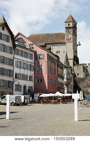 RAPPERSWIL SWITZERLAND - MAY 10 2016: The 13th century castle with a clock tower towering over the buildings of the city can be seen from the side of town square
