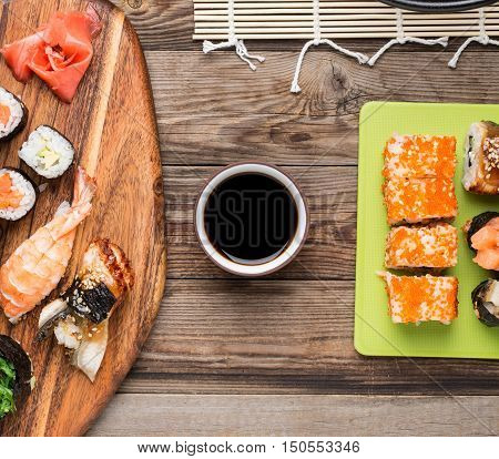 Set of sushi rolls and sashimi with soy sauce on wooden background, top view