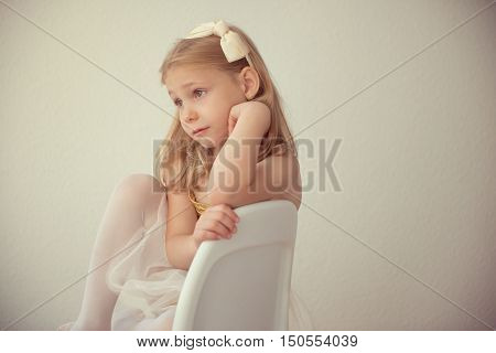 Pretty Seriously Ballet Girl In White Tutu Sitting On Chair