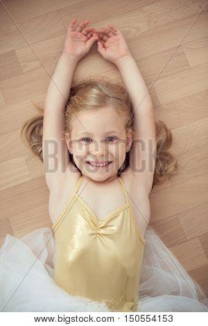 Pretty Smiling Ballet Chilg Girl In White Tutu On Floor