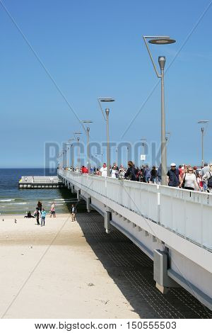 KOLOBRZEG POLAND - JUNE 19 2016: Contemporary version of the pier over the Baltic Sea waters and it is after general overhaul that was done in 2014. Many vacationers can be seen on the pier.