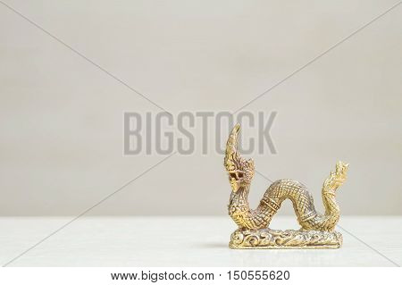 Closeup small brass king naga statue for worship and decorate on blurred wood desk and wood wall in room textured background