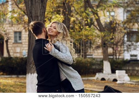 fashion outdoor photo of beautiful tender couple, wearing cozy clothes, walking by autumn park