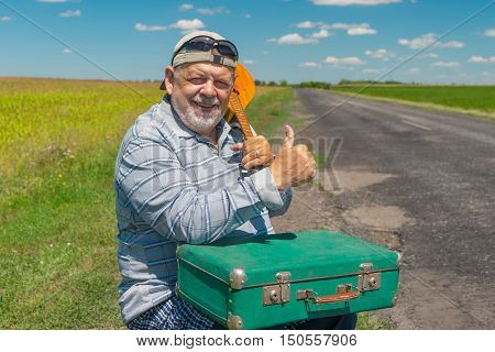 Portrait of smiling senior hiker having short rest on a roadside with ancient green suitcase and mandolin