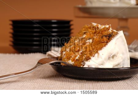 Piece Of Carrot Cake With Plates In Background