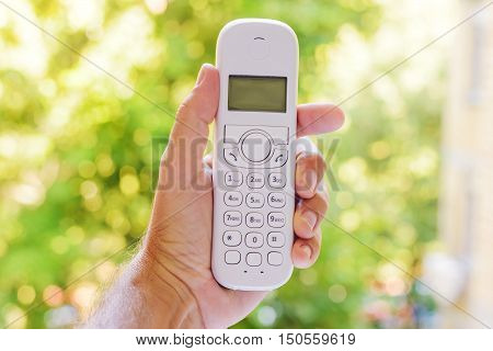 Male hand holding cordless landline telephone receiver outdoors selective focus