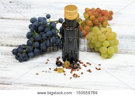 Grape seed oil and grape seeds in front fresh grapes around