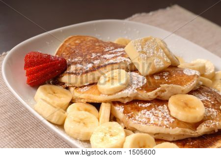 Banana Pancakes With Maple Syrup And A Strawberrry