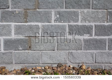 grey brick wall for with the rocks below background or web design
