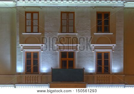 Several windows in a row and balcony on night illuminated facade of urban apartment building front view St. Petersburg Russia