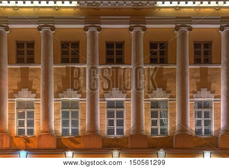 Several windows and columns in a row on night illuminated facade of Naval Academy front view St. Petersburg Russia