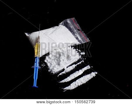Injection syringe on cocaine drug powder pile and lines and cocaine bag on black background