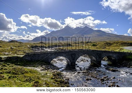 Old three arched stone bridge over the River Sligachan in Isle of Skye Scotland with Cuillin mountain range in the distance