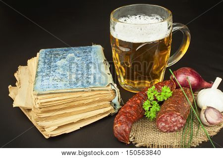 Glass of beer, bratwurst and a book on wooden background. Relax with a book.