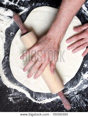 A rolling pin flattening a pizza
