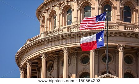 American and Texas state flags flying on the dome of the Texas State Capitol building in Austin
