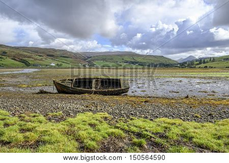 Beautiful Isle of Skye Scotland landscape. Old abandoned broken wooden row boat wreck covered in barnacles and seaweed on the shore at Loch Harport at low tide