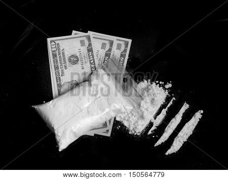 Cocaine drug powder in bag on dollar bills, cocaine pile and lines on white background in black and white colors