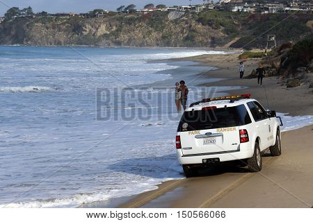 Laguna Beach, California, USA, October 2, 2016--Couple watches as park ranger vehicle drives on sand near water's edge at Salt Creek Beach in Southern California.