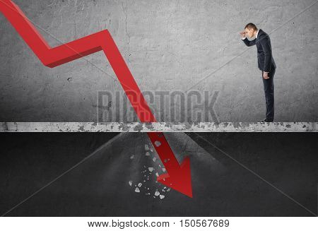 Businessman looking down at the falling red arrow destroying a concrete barrier. Collapse and drop. Fall and depreciation. Regression and deterioration. Crisis.
