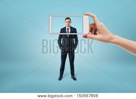 Face of businessman in focus seeing through the frame of phone. Photograph. Drive into the frame.