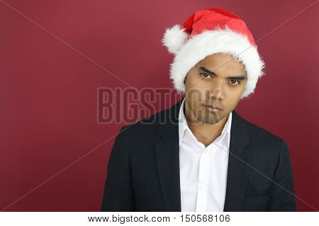 Young serious man wearing a Santa hat