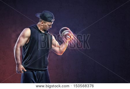 Muscular young guy lifting a dumbbell to training his biceps. Power training. Healthy lifestyle. Fitness and sport. Biceps Exercises.