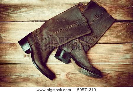 Stylish female brown boots in wooden background