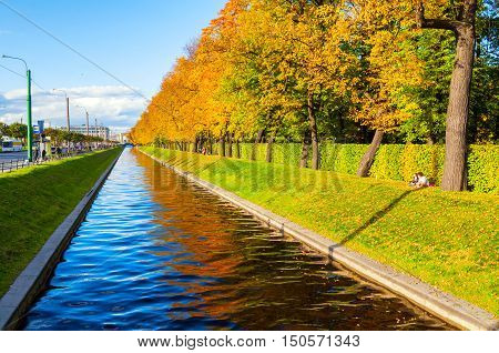 ST PETERSBURG RUSSIA-OCTOBER 3 2016. Autumn landscape of St Petersburg - Swan Canal and autumn park with golden autumn trees in sunny weather. St Petersburg autumn city landscape