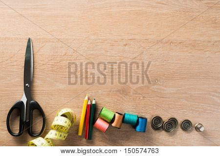 Old scissors bobbins threads material on wooden table