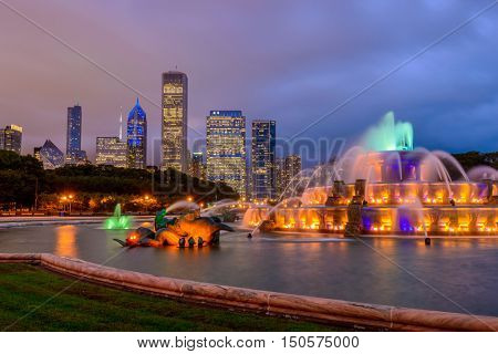 Chicago skyline panorama with skyscrapers and Buckingham fountain in Grant Park at night lit by colorful lights.