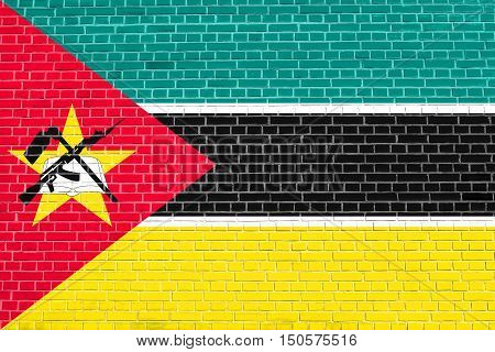 Mozambican national official flag. African patriotic symbol banner element background. Accurate dimensions. Correct size colors. Flag of Mozambique on brick wall texture background, 3d illustration