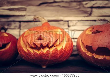 Halloween spooky pumpkins on rustic stone background